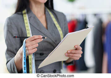 Woman seamstress writing down measurements on paper with pencil closeup. Female business concept