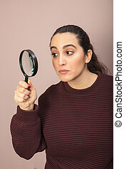 Woman searching for clues with a magnifying glass