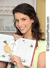 Woman searching for recipe in cook book