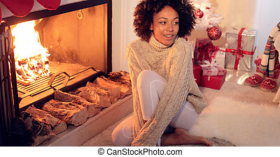 Woman seated by fireplace and holiday setting