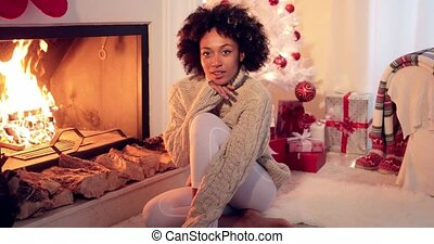 Woman seated by fireplace and holiday setting and wearing...