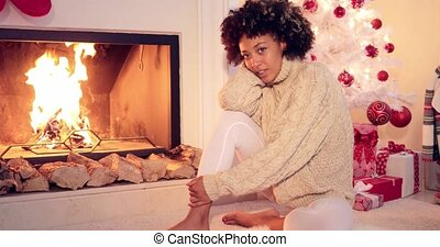 Woman seated by fireplace runs hand in her hair