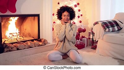Woman seated by white christmas tree and presents beside...