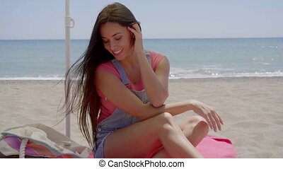 Woman seated in shade at beach with hand on neck