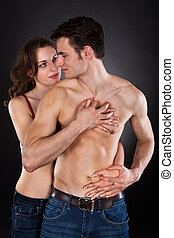 Woman Seducing Man Over Black Background