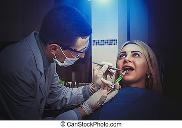 Woman seeing a dentist - Young dentist treating woman in the...
