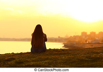 Woman seeing a sunset on the city