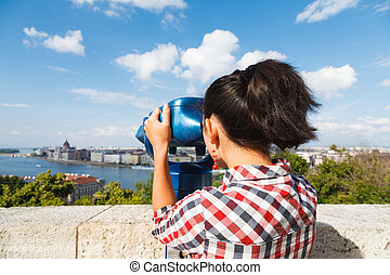 Woman seeing the city over a river through binocular.