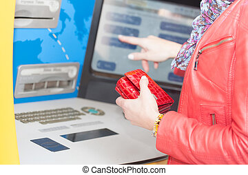 Woman selecting a transaction on a bank ATM using her finger...