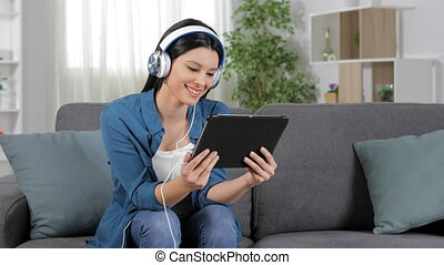 Woman selecting and watching media at home - Happy woman...