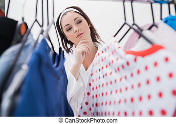 Woman selecting clothing - Young woman looking at clothing...