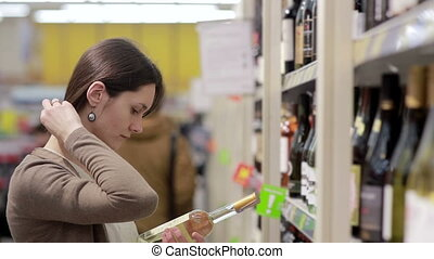 Woman selects the wine on the shelves in the store - Woman...
