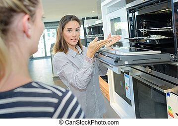 woman selling a kitchen oven in store
