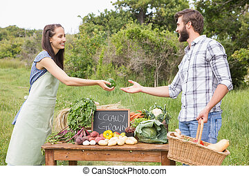 Woman selling organic vegetables at