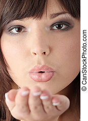 Young beautiful woman sending a kiss, isolated on white