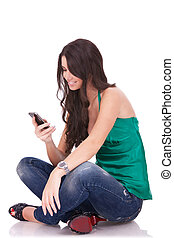 woman sending an sms - Portrait of a beautiful woman seated ...