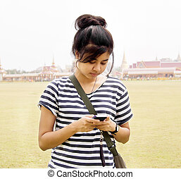 Woman sending / receiving a text message / email on her mobile / cellular phone.