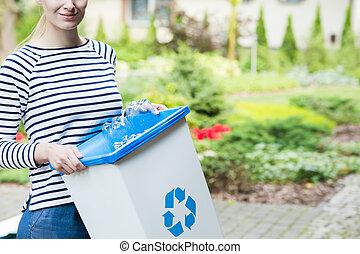 Woman separating plastic bottles