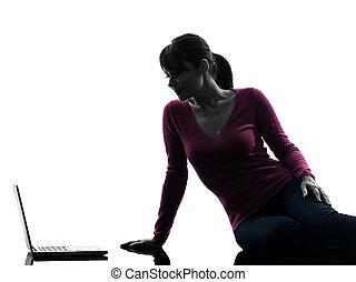 woman serious computing laptop computer silhouette