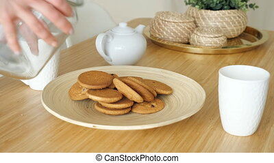 woman serves breakfast with biscuits on table in kitchen -...