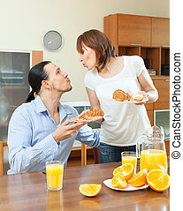Woman serves croissants and scrambled eggs her beloved man