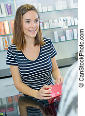 Woman serving customer in cosmetics store