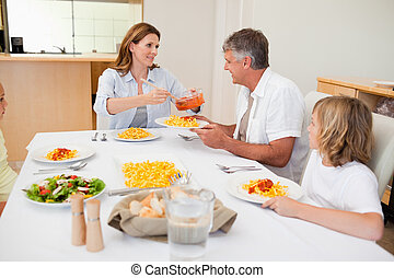 Woman serving dinner to hungry family