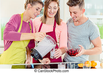 Woman serving fresh smoothie to her friends