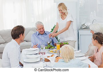 Woman serving salad at the dinner table