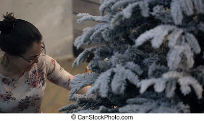 Woman sets and preparing the Christmas tree to decorate the room.