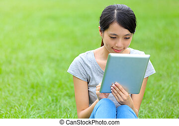 Woman setting on grass with tablet