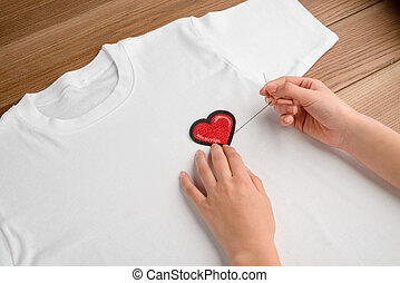 Woman sewing an embroidered heart patch to a plain white t-shirt