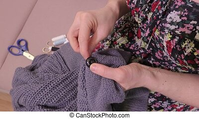 Woman sewing button on jumper