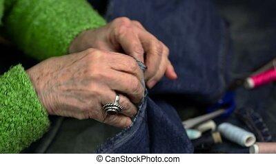 Woman sewing denim fabric