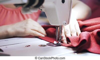 Woman sewing red fabric and cutting excessive material