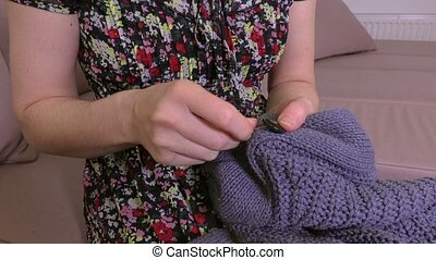 Woman sews button on cardigan