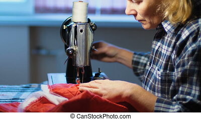 Woman sews on old sewing machine at home