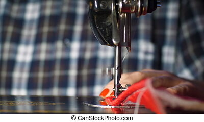 Woman sews on old sewing machine at home - Shoot of woman...