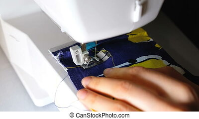 Woman sews on the sewing machine completes sewing close-up