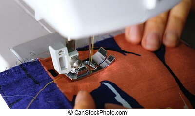 Woman sews on the sewing machine, paving the line and...