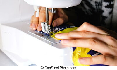 Woman sews on the sewing machine