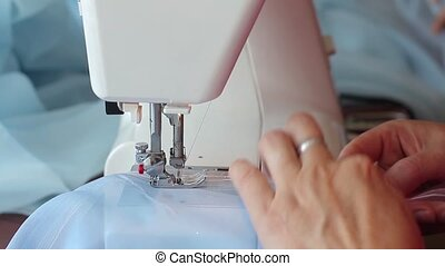 Woman sews on the sewing machine. Women's hands. Close-up.