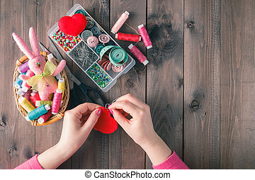 Woman sews red heart shaped toy by needle