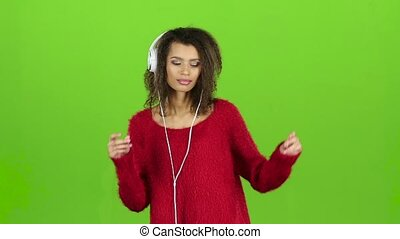 Woman sexually dances with headphones on green screen. Slow motion