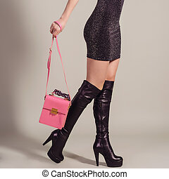Woman sexy legs in jackboots with handbag. Shopping and business