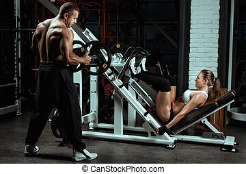 Woman shakes her legs over the bar. Man coach puts weight on...