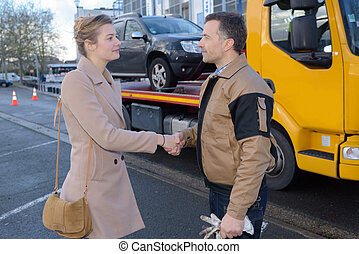 Woman shaking hands with man who has recovered her car