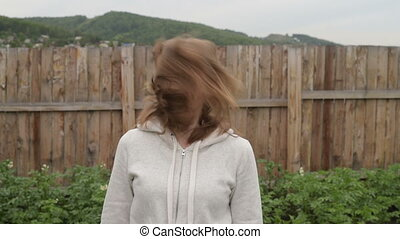 Woman shaking her head in the garden
