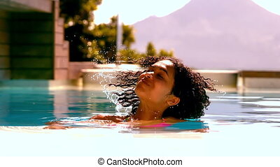 Woman shaking her wet hair in swimming pool