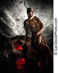 Woman shaman in ritual garment siting on skull